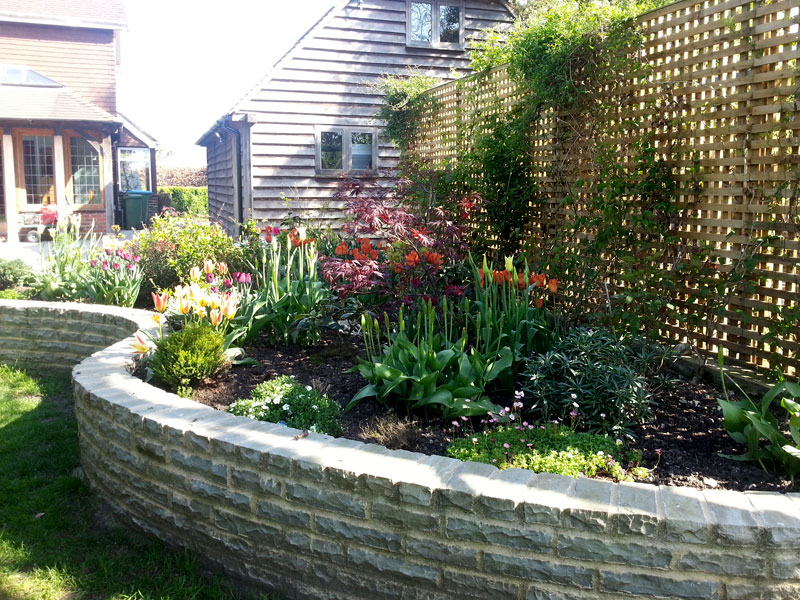 Fully planted raised stone wall flowerbeds and trellis