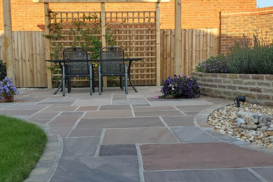 New garden design project by Shakespeare's Landscapes with paving, pergola and seating area, raised flower beds, a water feature, lawn and lighting.
