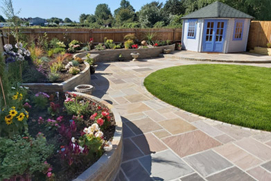 Extensive garden design by Shakespeare's Landscapes featuring Indian sandstone paving, summerhouse, raised flowerbeds, rock and pebble water feature.