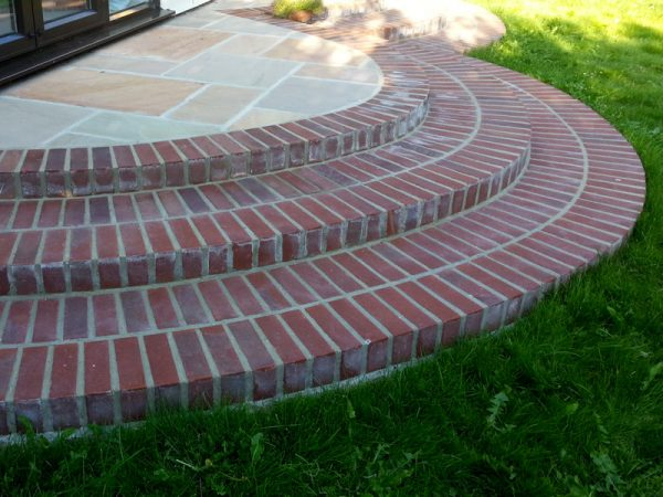 Brick steps leading to patio door by Shakespeare's Landscapes