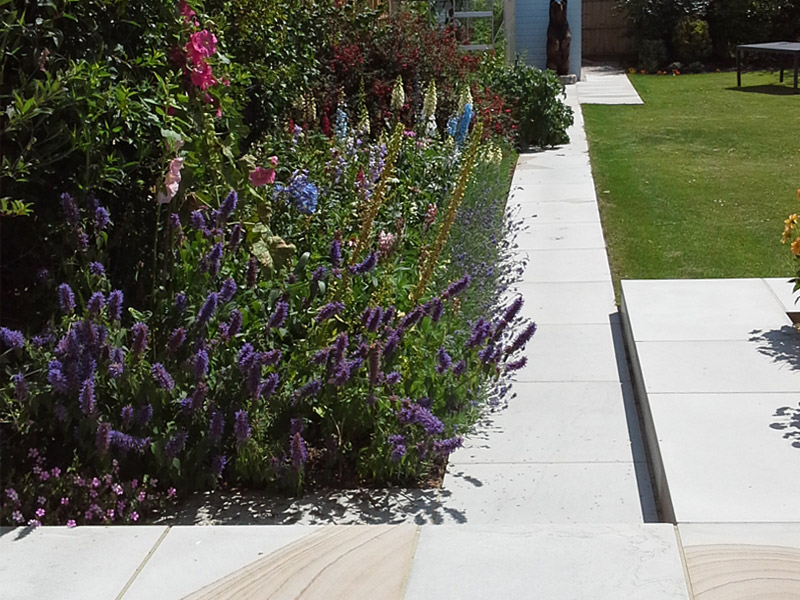 Paved path in an established garden by Shakespeare's Landscapes